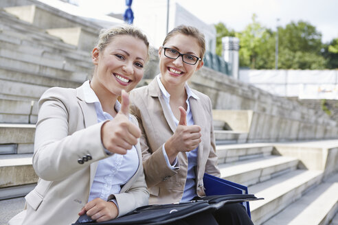 Germany, Cologne, Two businesswomen sitting on stairs, giving thumbs up - RKNF000130