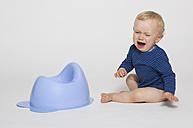 Crying baby boy sitting next to his potty, studio shot - MUF001388