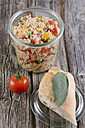 Couscous salad in glass jar with baguette bread and tomatoes, close up - ODF000477