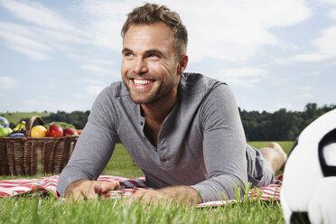 Germany, Cologne, Man lying on picnic blanket, smiling - PDF000394