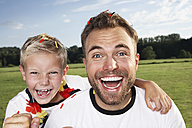 Germany, Cologne, Father and son supporting their soccer team - PDF000412