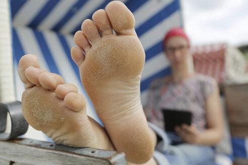 Germany, Lower Saxony, East Frisia, Langeoog, woman reading e-book at the beach - JATF000310