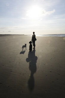 Germany, Lower Saxony, East Frisia, Langeoog, shadows and silhouettes of a woman and her dogs at the beach - JATF000360
