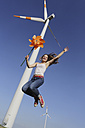 Germany, North Rhine Westphalia, Neuss, female teenager at wind farm jumping in the air with windmill in her hand - JATF000328