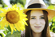 Germany, Cologne, young woman with hat and sunflower - JATF000332