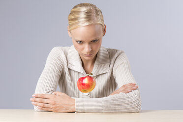 Young woman looking at flying apple - DRF000217