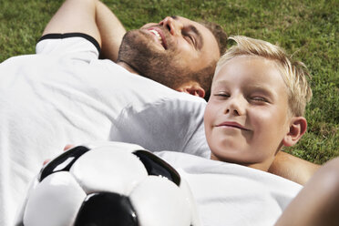 Germany, Father and sun lying on lawn, wearing football shirts - PDF000440