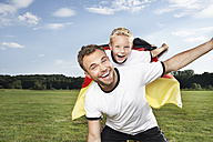 Germany, Cologne, Father and son cheering in football outfit - PDF000443
