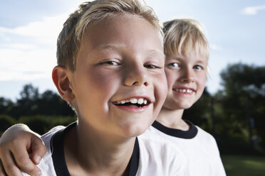 Germany, Cologne, Two boys playing football, wearing football shirts - PDF000455
