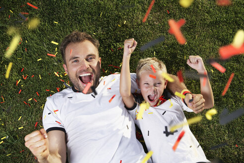 Germany, Father and son lying on lawn, wearing football shirts, cheering - PDF000458