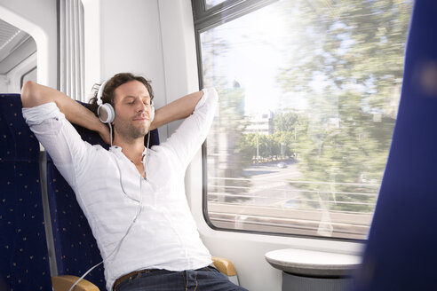 Man with headphones in a train - KFF000258