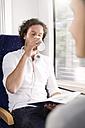 Man drinking coffee in a train - KFF000255