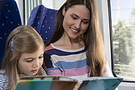 Mother and daughter reading book in a train - KFF000246