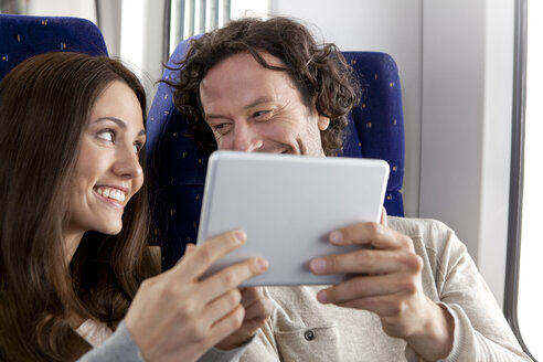 Couple using digital tablet in a train - KFF000235