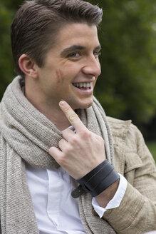 Smiling man showing at lipstick mark on his cheek - DAWF000003