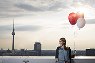 Germany, Berlin, Young woman on rooftop terrace, holding balloons - FKF000283