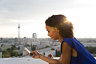 Germany, Berlin, Young woman using mobile phone - FKF000288