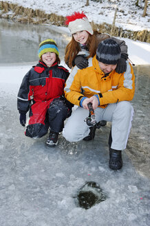 Father with daughter and son ice fishing on a lake - LB000296