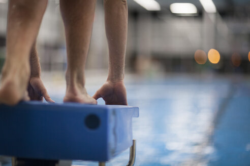 Swimmer on starting block at indoor swimming pool - SEF000079