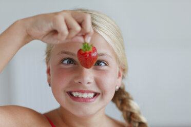 Smiling blond girl looking at strawberry - HR000010