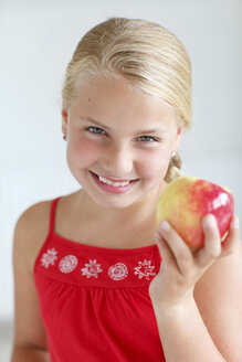Smiling blond girl holding an apple - HR000013