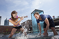Germany, Bavaria, Munich, Couple splashing with water at fountain - RBF001353