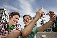 Germany, Bavaria, Munich, Two friends with smartphone taking self-portrait - RBF001361