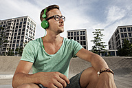 Germany, Bavaria, Munich, Young man listening to music - RBF001329