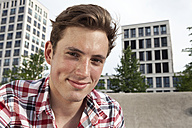 Germany, Bavaria, Munich, Smiling young man outdoors, portrait - RBF001327
