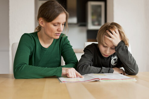 Germany, Rhineland-Palatinate, Neuwied, woman helping her son by doing his school work - PA000016