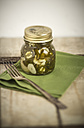 Pickled and sliced Jalapeno-Chilis (Capsicum annuum) in a jar, green serviette and fork, studio shot - SBDF000228
