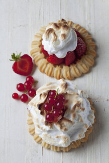 Two meringue tartlets with red currants and strawberries on wood, studio shot - CSF020095