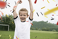 Boy in soccer jersey cheering on soccer pitch - PDF000461
