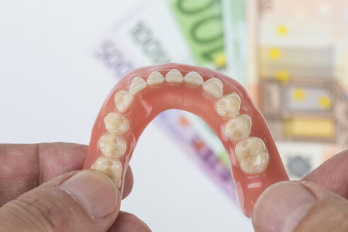 Hand holding dentures with Euro notes in background - DRF000229