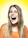Portrait of screaming young woman, studio shot - STKF000358