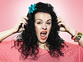 Portrait of screaming young woman with headphones, studio shot - STKF000361