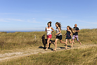 France, Bretagne, Ste Marguerite, Landeda, Finistre, parents and two daughters running with her dog on a dune at Atlantic - LAF000192