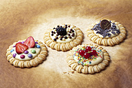 Four pies with vanilla pudding and different toppings, studio shot - CSF020124