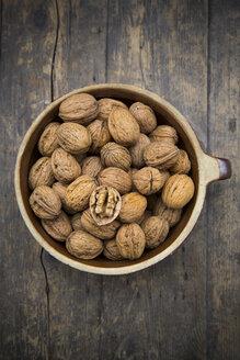 Earthenware bowl with walnuts (Juglans regia) on wooden table, studio shot - LVF000221