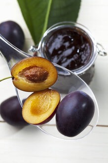 Glass of plum jam and some plums on plastic spoon, studio shot - CSF020156
