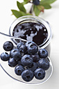 Glass of blueberry marmelade and some berries on plastic spoon, studio shot - CSF020150