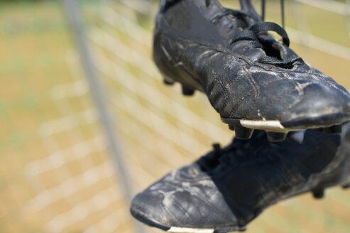 Germany, Bavaria, Munich, football shoes hanging in football net - ASF005202