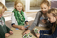 Four children playing card game in living room - GDF000220