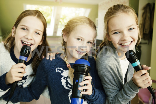 Three girls singing with microphone - GDF000231