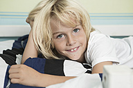 Smiling blond boy lying in bed, portrait - GDF000235