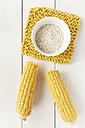 Sweetcorn cobs and arborio rice on white wooden table, studio shot - EVGF000244