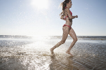 Germany, St Peter-Ording, young woman running at beach - RB001389