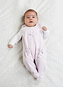 Female baby wearing pink rompers lying on white cloth - WWF003230