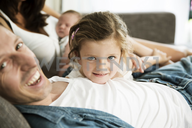 Young parents with male newborn and little daughter sitting on sofa at home - JATF000388 - Jan Tepass/Westend61