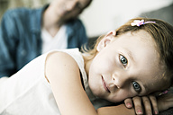 Thoughtful little girl lying on sofa, her father standing in the background - JATF000394